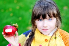 Funny child girl eating apple outdoors Stock Photos