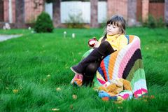 Funny child girl eating apple outdoors Royalty Free Stock Photography