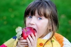 Funny child girl eating apple outdoors Royalty Free Stock Photos