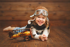 Funny child girl pilot aviator with airplane laughing. On wooden background Stock Photos