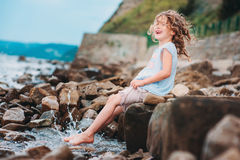Funny child girl playing with water splash on the beach. Traveling on summer vacation. Happy childhood concept Stock Photography