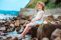 Funny child girl playing with water splash on the beach. Traveling on summer vacation. Stock Photos