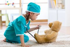 Funny child girl pretending she is a doctor in hospital stock photos