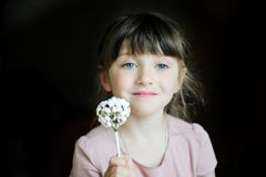 Funny child girl showing a marshmallow cake Royalty Free Stock Image