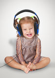 Funny child girl with tatoo listening music with headphones Royalty Free Stock Image