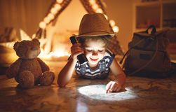 Funny child girl tourist with flashlight and world map and backp Royalty Free Stock Photos