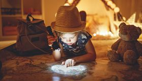 Funny child girl tourist with flashlight and world map and backp. Funny happy child girl tourist with flashlight and world map and backpack stock photo