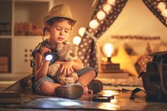 Funny child girl tourist with flashlight and world map and backp Stock Image