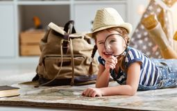 Funny child girl tourist with world map, backpack and magnifier. Funny happy child girl tourist with world map, backpack and magnifier royalty free stock photography