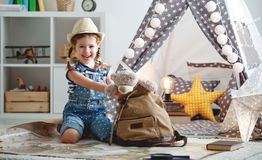 Funny child girl tourist with world map, backpack and magnifier Royalty Free Stock Photo