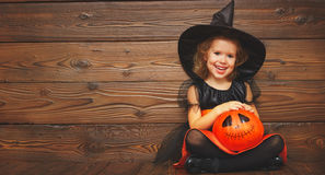Funny child girl in witch costume  for Halloween with pumpkin Ja Stock Photos