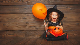 Funny child girl in witch costume  for Halloween with pumpkin Ja. Funny child girl in witch costume for Halloween with pumpkin Jack and orange balloon on a dark Stock Photos
