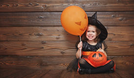 Funny child girl in witch costume  for Halloween with pumpkin Ja Royalty Free Stock Image