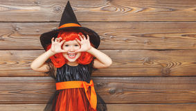 Funny child girl in witch costume for Halloween scares Royalty Free Stock Images