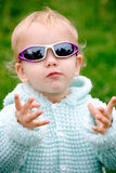 Funny child in glasses. On green natural background stock photography