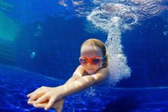Funny child in goggles dive in swimming pool. Happy family in swimming pool. Smiling child in goggles swim, dive in pool with fun - jump deep down underwater royalty free stock photography