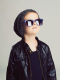 Funny child in hat and sunglasses.fashionable little boy. Winter fashion trendy kids stock photography