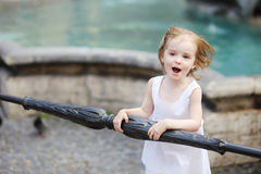 Funny child having fun by a city fountain Stock Images