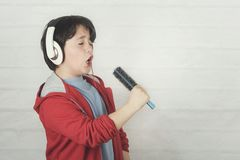 Funny child in headphones singing with hair brush royalty free stock photos