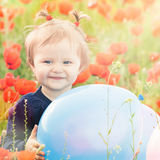 Funny child holding a balloon outdoor at poppy field Royalty Free Stock Image