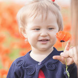 Funny child holding a balloon outdoor at poppy field Stock Photos