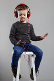 Funny child.little boy in headphones sitting on chair.listening music Stock Photography
