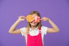 Funny child with lollipops on violet background. Girl smiling with candy eyes. Little kid smile with candies on sticks royalty free stock image