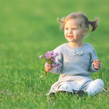 Funny child outdoor at flowers field holding flowers. Autumn season Royalty Free Stock Photo