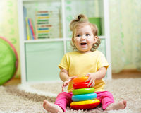 Funny child playing with color toy indoor Stock Photography