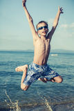 Funny child playing in sea splashing water and jumping. Stock Photos