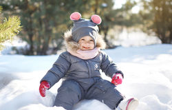 Funny child playing on the snow in sunny winter day Royalty Free Stock Images