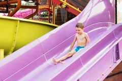 Funny child playing in water park splashing water. Summer holidays concept. Boy has into pool after going down water slide during. Summer. Kid on water slide at stock images
