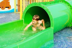 Funny child playing in water park splashing water. Summer holidays concept. Boy has into pool after going down water slide during. Summer. Kid on water slide at royalty free stock photos