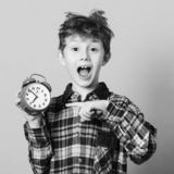 Funny child pointing at alarm clock. Excited boy overslept before school. Child back to school. Isolated on yellow. Education and stock image