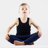 Funny child practicing yoga. little Boy does yoga Royalty Free Stock Photo
