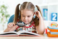 Funny child reads book using magnifier sitting at Royalty Free Stock Photography
