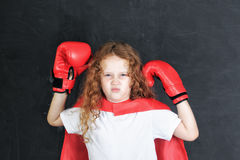 Funny child in red boxing gloves showing muscles stand near chal Royalty Free Stock Photos