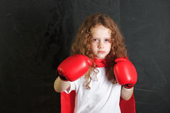 Funny child in red boxing gloves showing muscles stand near chal Stock Photography