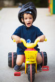 Funny child riding tricycle Stock Photos