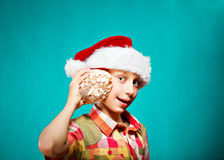 Funny child Santa holding a big sea shell smiling. Winter holidays concept. Stock Photos