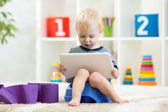 Funny child sitting on chamber pot with tablet computer. Funny child boy sitting on chamber pot with tablet computer stock images