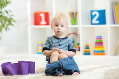Funny child sitting on chamber pot with toilet paper rolls. Funny child boy sitting on chamber pot with toilet paper rolls stock images