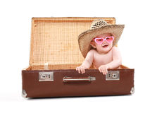 Funny child in sunglasses and summer straw hat. Looks out of a suitcase, tours, travel, vacation - concept Stock Photography