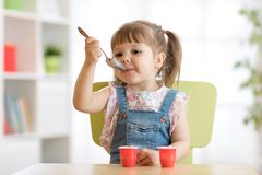 Funny child eating healthy food with a spoon at home. Funny child toddler eating yoghurt with a spoon at home Royalty Free Stock Images