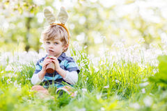 Funny child wearing Easter bunny ears and eating chocolate at sp. Funny child wearing Easter bunny ears at spring green grass and blooming apple garden, eating Royalty Free Stock Image