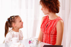 Funny child and young girl drinking tea Royalty Free Stock Image