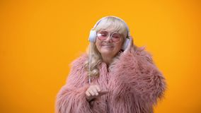 Funny childish aged lady in cute outfit pretending to be DJ, hobby and dreams. Stock footage stock footage