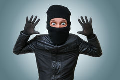 Funny childlike burglar puts hands up. Royalty Free Stock Photos