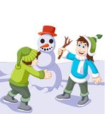 Funny children cartoon playing with snowman in snow of winter Royalty Free Stock Photo