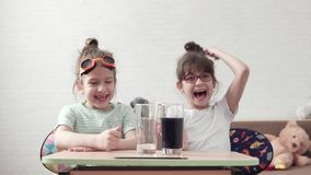 Funny children conduct a chemical experiment and mix reagents. kids are surprised and happy watching the chemical. Children conduct chemical experiments at home stock video footage